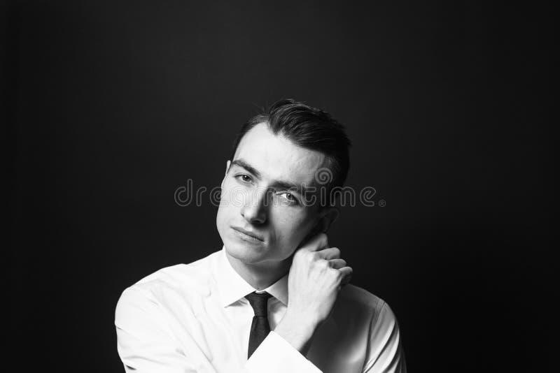 Stäng sig upp den svartvita ståenden av en ung man i en vit skjorta och smoking arkivfoton