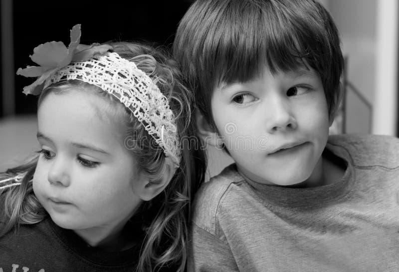 Stäng sig upp den svartvita ståenden av pojken och flickan, syskongruppen som kelar royaltyfria foton