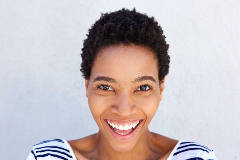 Stäng sig upp den unga afrikanska kvinnan som skrattar mot den gråa väggen royaltyfri bild