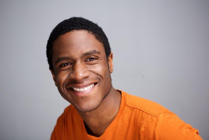 Stäng sig upp den unga svarta mannen som ler mot grå bakgrund fotografering för bildbyråer