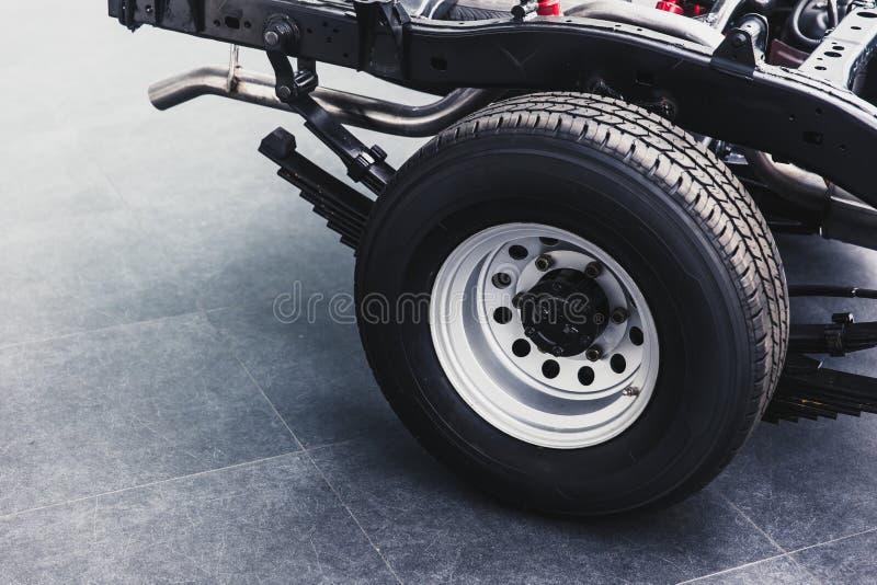 Stäng sig upp det bakre gummihjulet för pickupet med bilchassiunderbodyen arkivbilder