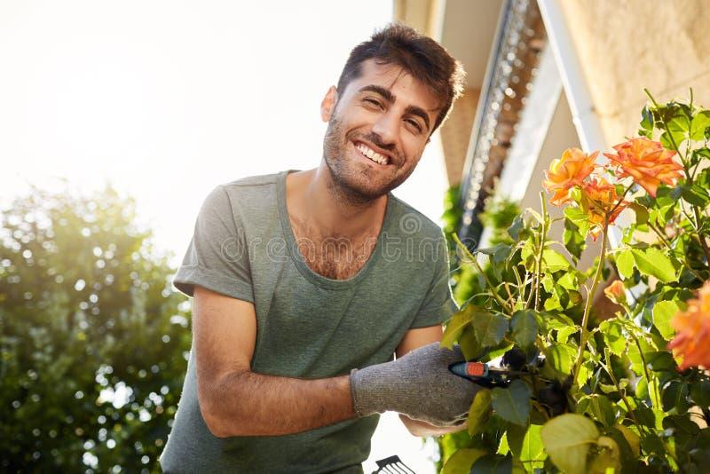Stäng sig upp det friaståenden av den unga gladlynta skäggiga mannen i blå t-skjorta som in camera som ler arbetar i trädgård med royaltyfri foto