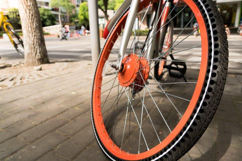 Stäng sig upp det orange cykelhjulet och gummihjulet arkivbild