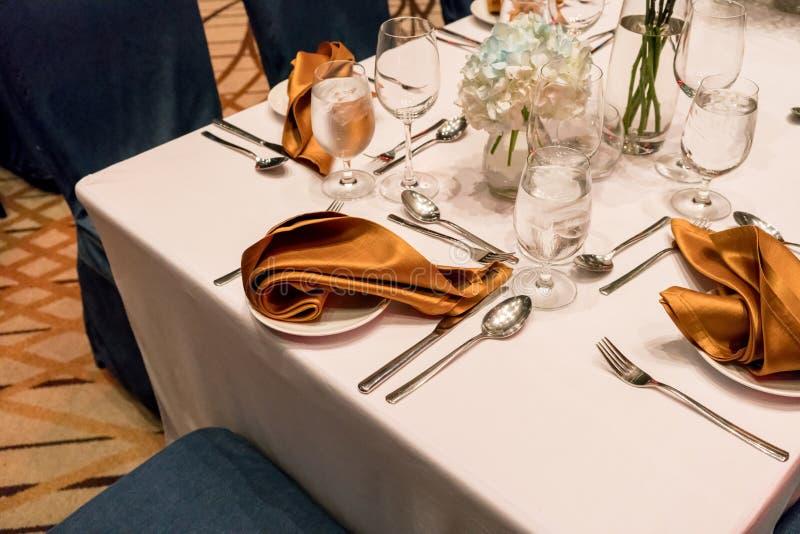Stäng sig upp detaljen av den guld- servetten och bestick på den eleganta tabellen royaltyfria bilder