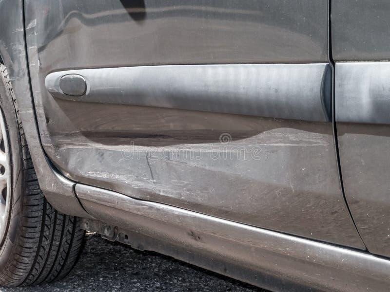 Stäng sig upp detaljen av en bucklig chauffördörr från en bilkrasch eller en bilolycka fotografering för bildbyråer