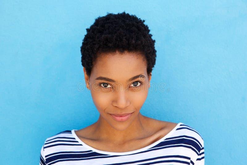 Stäng sig upp elegant ung afrikansk kvinna mot blå bakgrund royaltyfri foto