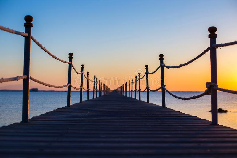 Stäng sig upp, en trämörk bro nära havet på den ljusa orange solnedgången, backgound, textur, tapeten, den fantastiska romantiska arkivfoto