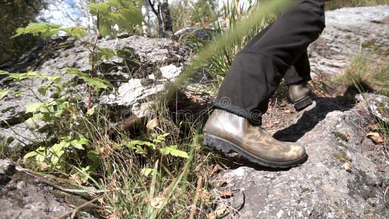 Stäng sig upp för att fotvandra gummistöveler i handling på en stenig bana Manliga görande moment som klättrar ett berg i en soli royaltyfria foton
