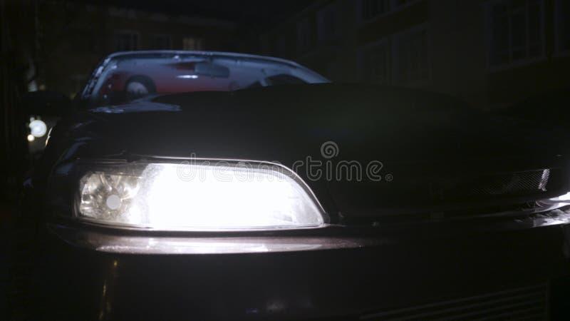 Stäng sig upp för billyktor av en parkerad passagerarebil som vänder på på natten, bildetaljbegrepp actinium Ett medelanseende royaltyfri bild