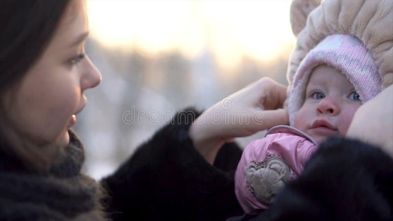 Stäng sig upp för den lyckliga härliga modern som trycker på hatten av älskvärt, behandla som ett barn flickan i vinter parkerar, royaltyfria bilder