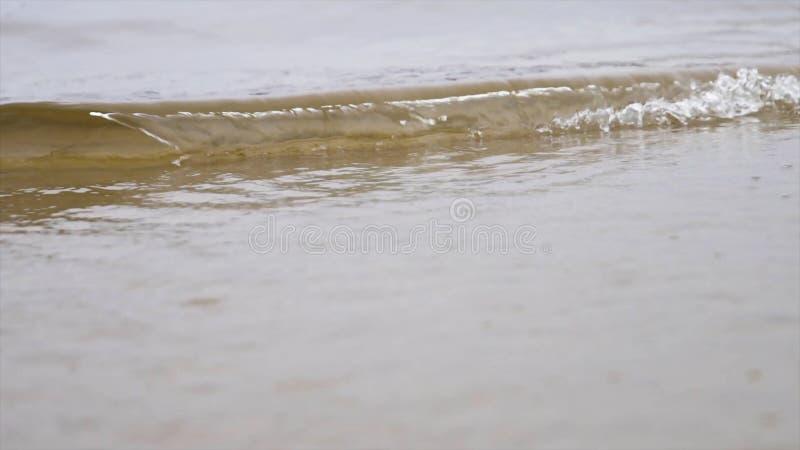 Stäng sig upp för havsvattenvågorna på en sandig strand, naturlig bakgrund Materiell?ngd i fot r?knat Små vågor som tvättar sig u royaltyfria foton