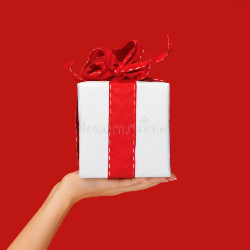 Stäng sig upp för julgåvan för handen den hållande asken över rött royaltyfria foton