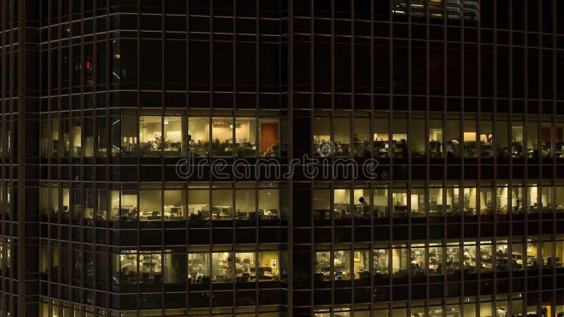 Stäng sig upp för skyskrapafönsterglöd på natten och folkinsidan, utelivbegrepp materiel Stäng sig upp för modernt kontor royaltyfri foto
