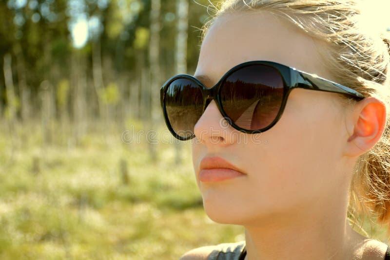 Stäng sig upp flickaståenden med vandringsledreflexion på solglasögon royaltyfria foton