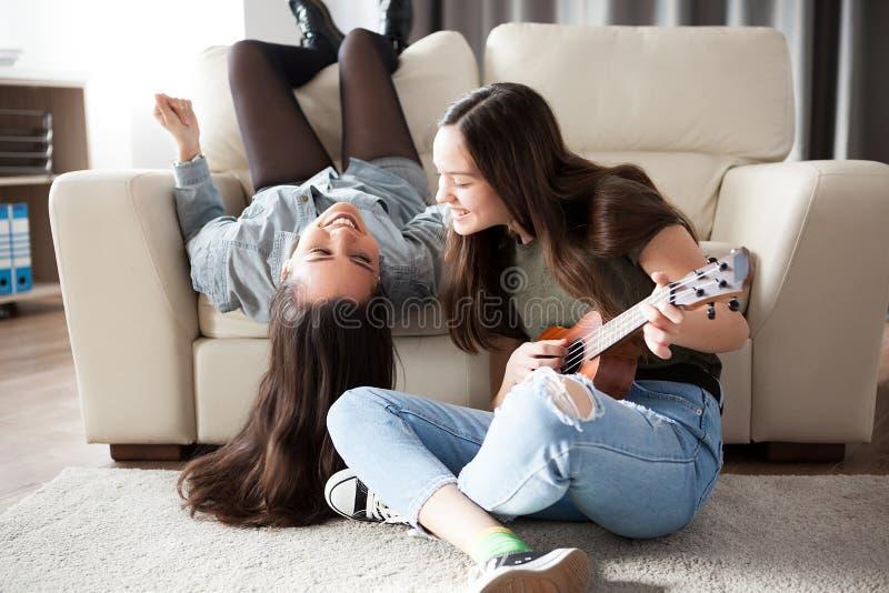 Stäng sig upp flickvänner i vardagsrummet som har gyckel royaltyfria foton