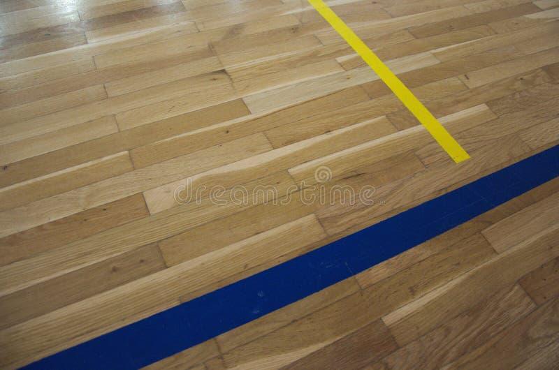 Stäng sig upp fotoet av den gamla parketten med linjer i skolasportidrottshall royaltyfria bilder