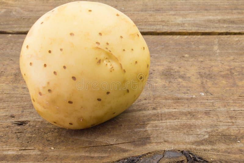 Stäng sig upp fotoet av en potatis på lantligt trä arkivfoto