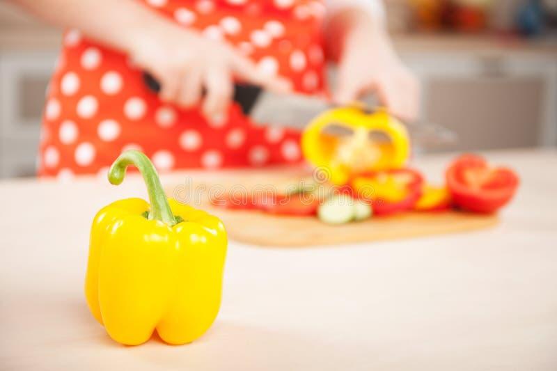 Stäng sig upp fotoet av kvinnan som hugger av paprika för sallad royaltyfri bild