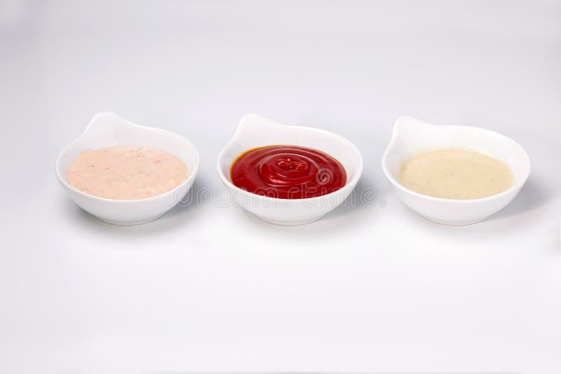 Stäng sig upp fotoet av tre olika doppa dressingsåser royaltyfria bilder