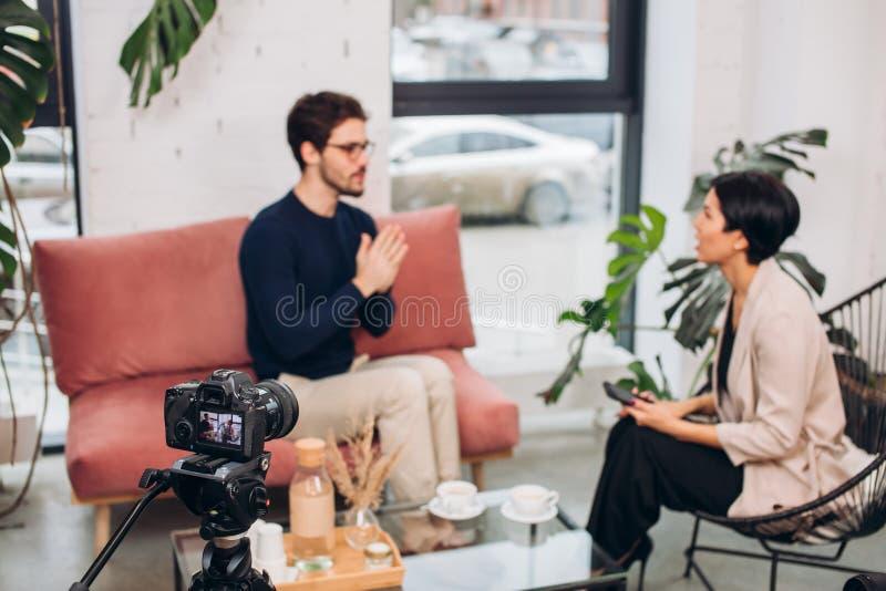 Stäng sig upp fotoet ung begåvad journalist som frågar några frågor till en manlig författare royaltyfria bilder