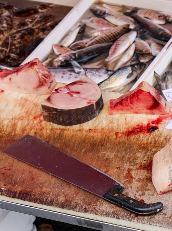 Stäng sig upp fotografi av den skivade döda fisken på en trätabell med blod och den stora köttyxan Djurt missbrukbegrepp, grymhet royaltyfria foton