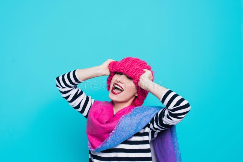 Stäng sig upp framsidaståenden av den toothy le unga kvinnan som bär den stack rosa hatten och halsduken fotografering för bildbyråer