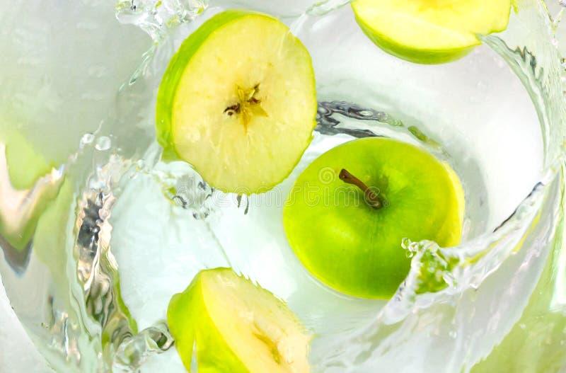 Stäng sig upp gröna äpplen som faller i vatten med färgstänk fotografering för bildbyråer