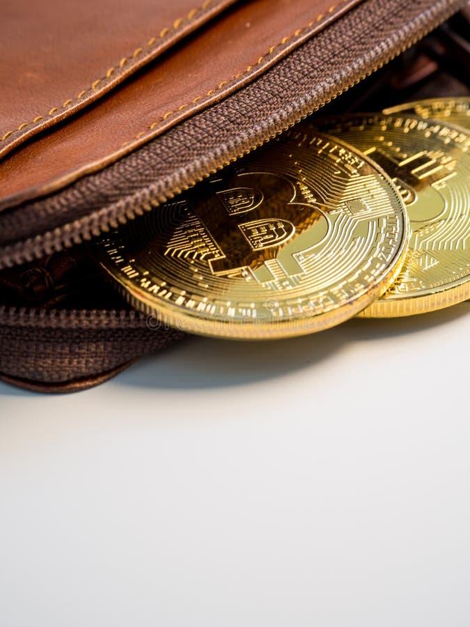 Stäng sig upp guld- mynt för bitcoin med plånboken på den vita bakgrunden Faktiskt cryptocurrencybegrepp arkivfoto