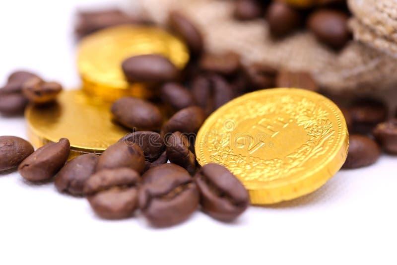 Stäng sig upp guld- mynt på kaffebönan, affär och kaffebegrepp arkivbild