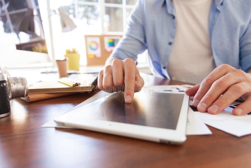 Stäng sig upp händer av den tryckande på minnestavlan för mannen, multitasking på skärmen i ett kontor royaltyfria foton