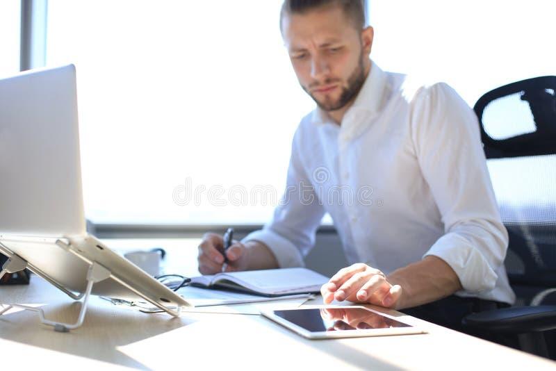 Stäng sig upp händer av den tryckande på minnestavlan för mannen, multitasking på skärmen i ett kontor royaltyfri fotografi