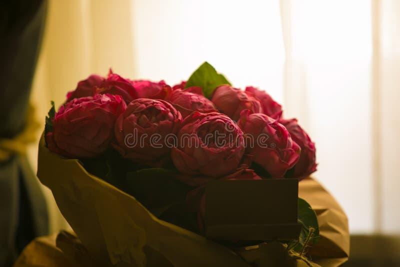Stäng sig upp härlig bukett för röda rosor med glödande ljus bakgrund för valentindag och älska temat arkivbild