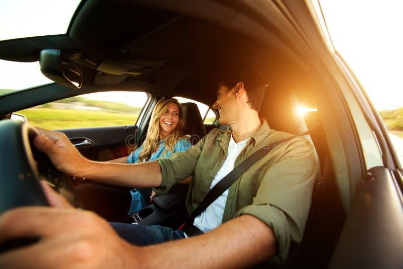 Stäng sig upp härliga par som skrattar i bil på vägtur royaltyfria bilder