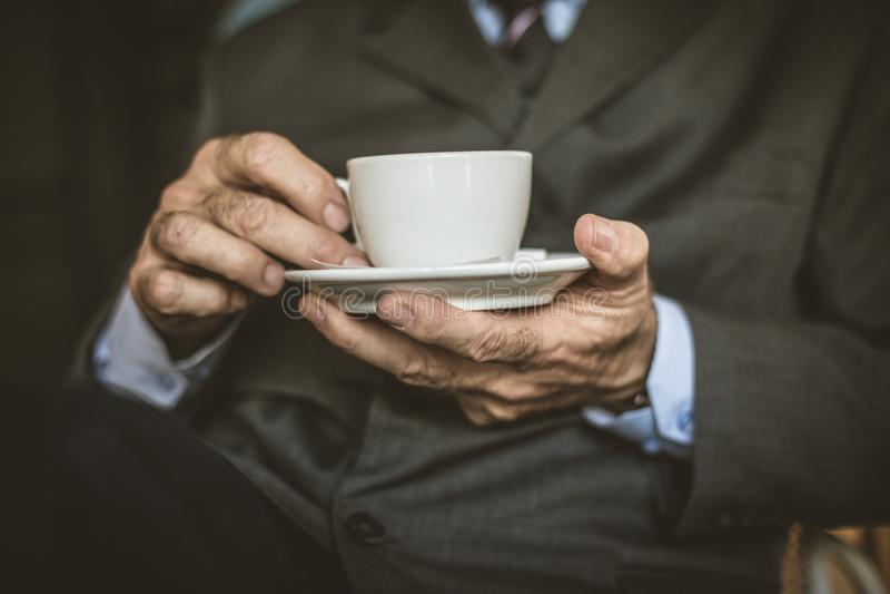 Stäng sig upp höga affärsmän för bild med en kopp kaffe royaltyfri foto
