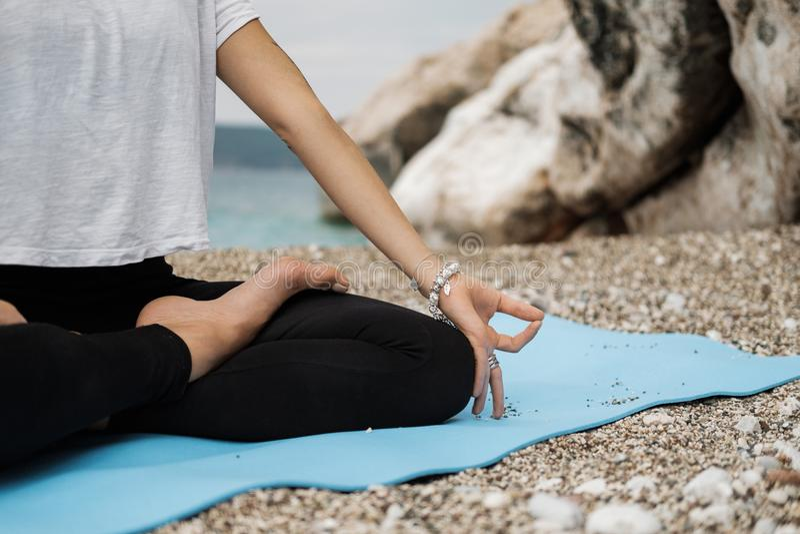 Stäng sig upp handen av kvinnan som gör en utomhus- Lotus Yoga Position och arkivfoto