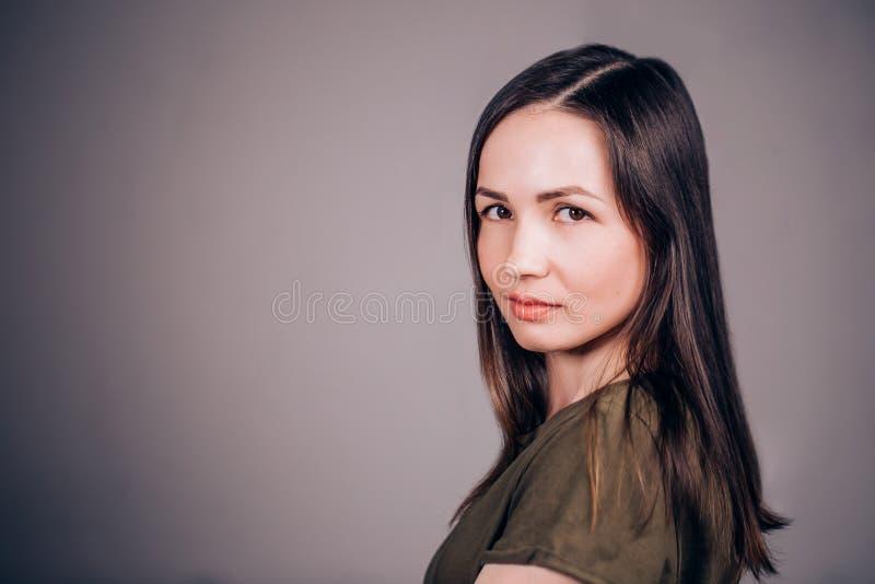 Stäng sig upp horisontalståenden av en ung brunettkvinna på en grå bakgrund charmigt flickaleende arkivbilder