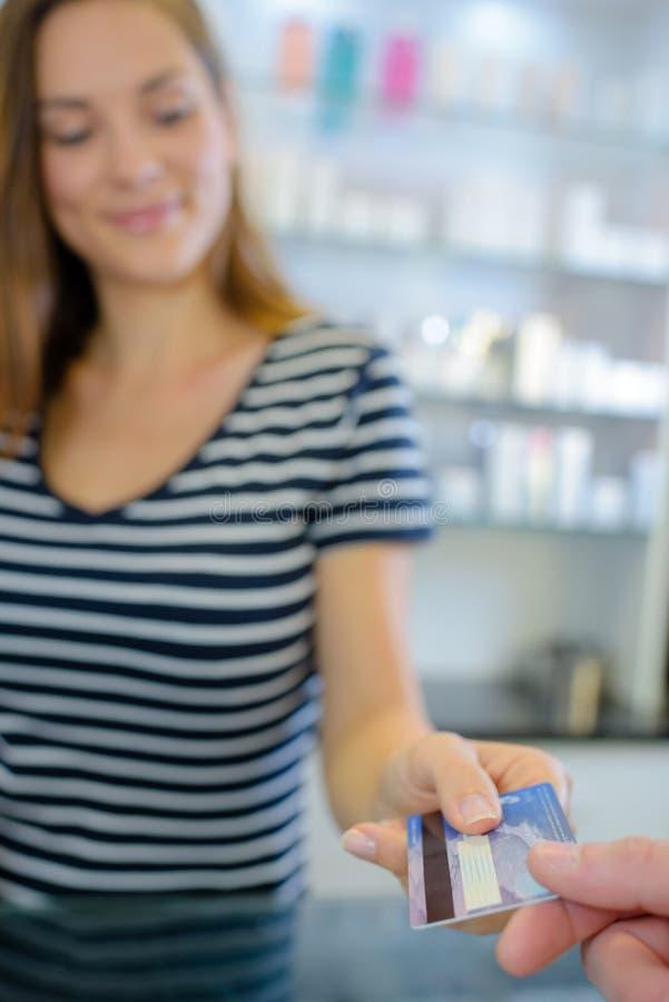 Stäng sig upp kunden som ger kreditkorten till den kvinnliga säljaren royaltyfria bilder