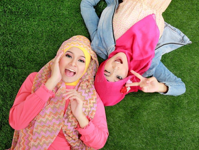 Stäng sig upp kvinnan för två den härliga lyckliga muslim som ligger på gräs royaltyfria bilder