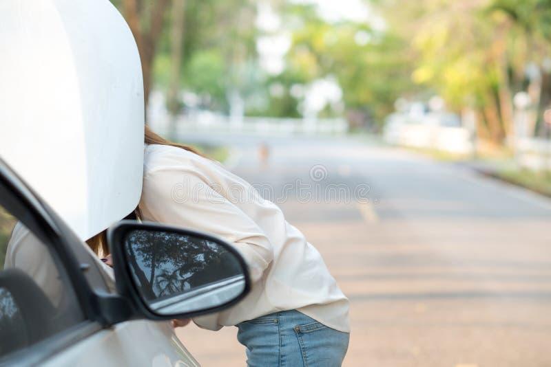 Stäng sig upp kvinnan som ner ser hennes brutna bil fotografering för bildbyråer