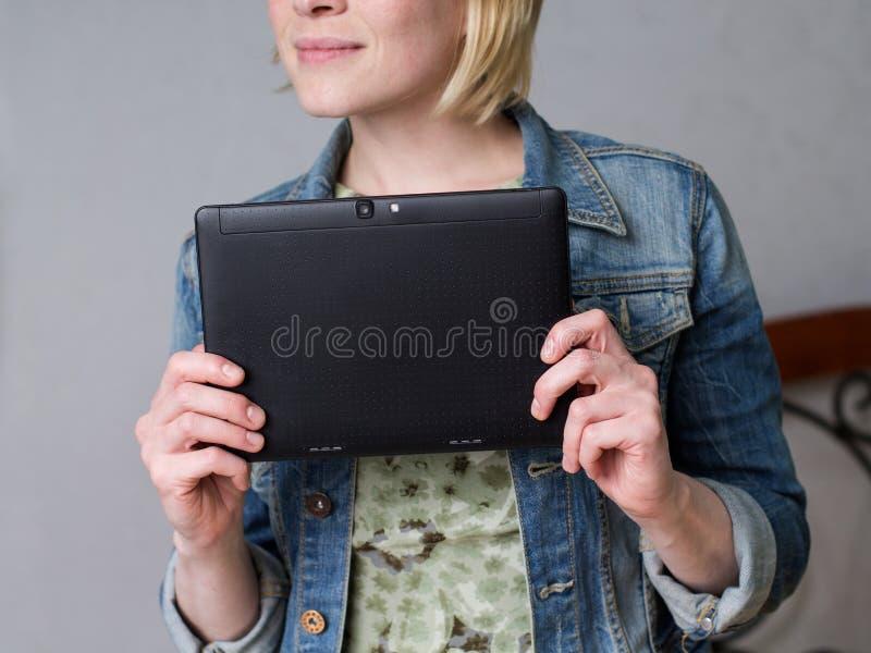 Stäng sig upp kvinnan som rymmer en minnestavla och le royaltyfria foton