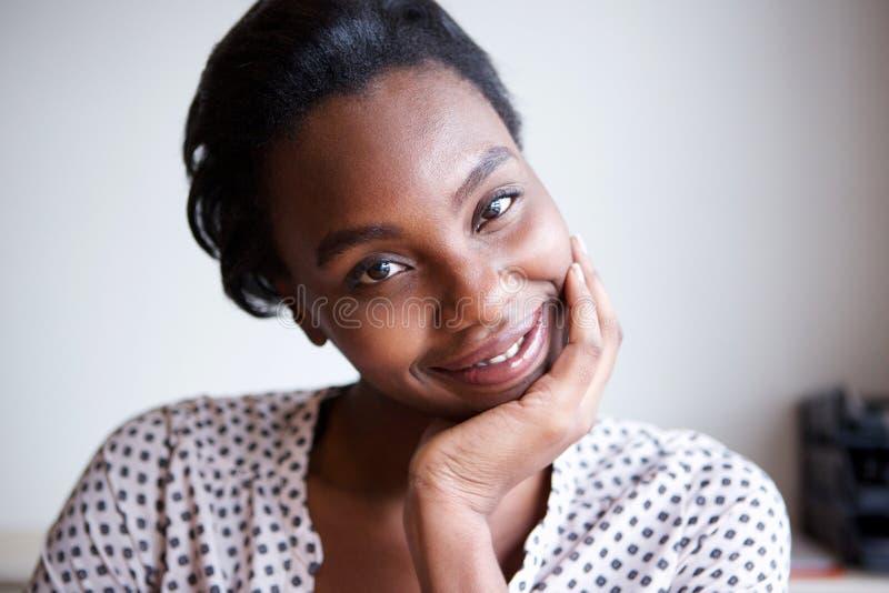 Stäng sig upp lycklig afrikansk amerikankvinnabenägenhet med huvudet i hand royaltyfri bild