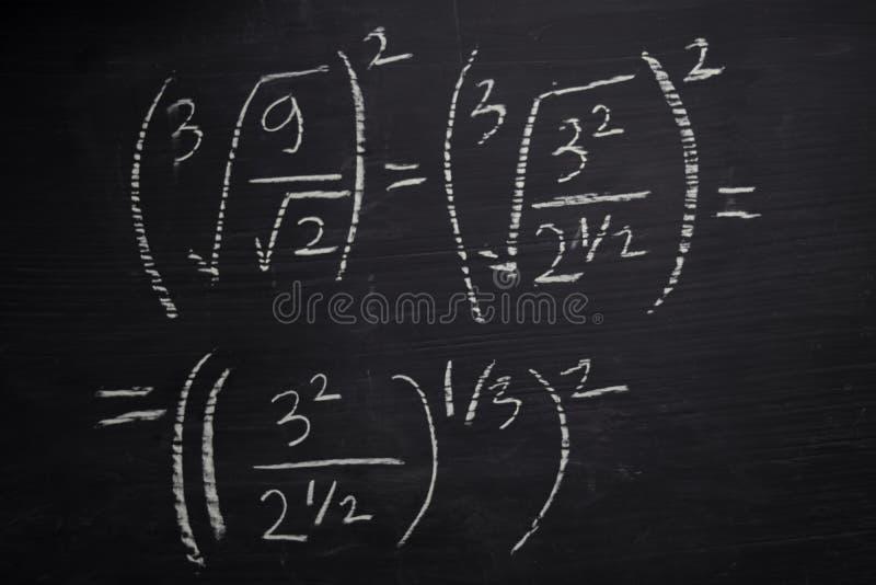 Stäng sig upp matematikformler som är skriftliga på en svart tavla books isolerat gammalt f?r begrepp utbildning royaltyfria foton