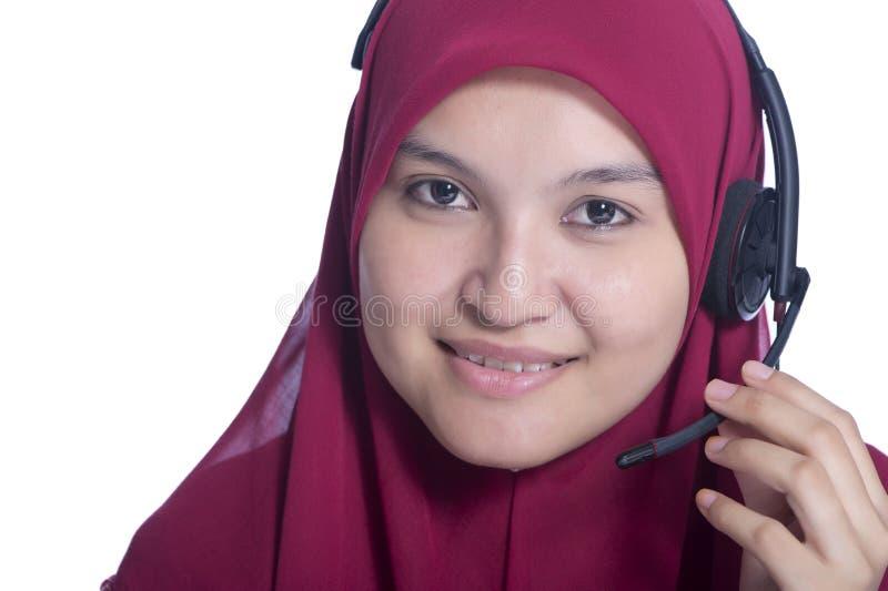 Stäng sig upp medel för Youngbeautiful muslimskt kvinnakundtjänst med hörlurar med mikrofon på vit bakgrund royaltyfria foton