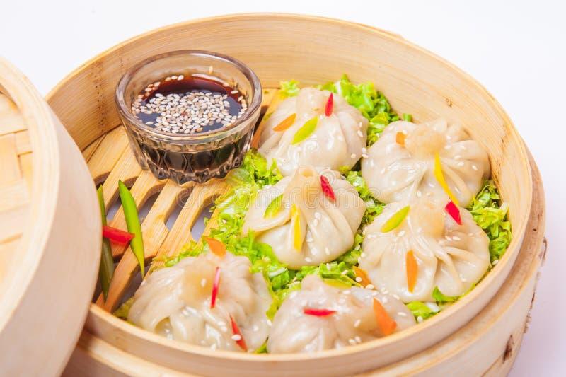 Stäng sig upp olik dim sum och sås i bambuångare på den isolerade vita bakgrunden Kinesisk kokkonst, selektiv fokus royaltyfri foto