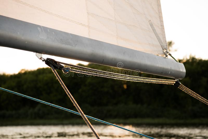 Stäng sig upp på bangmasten av en segla yacht, med segla och riggningrep, och flod- eller sjökusten i bakgrunden royaltyfria bilder