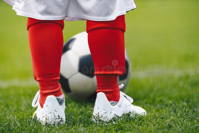 Stäng sig upp på ben av barnfotbollspelaren Ung fotboll för pojkeungeövning på gräsfält fotografering för bildbyråer
