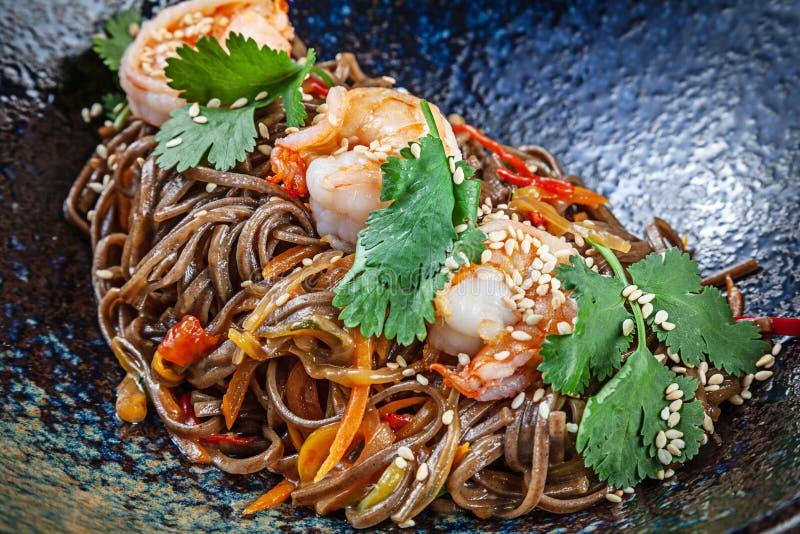 Stäng sig upp på bovetenudlar med räkor som tjänas som i svart texturerad bunke thai kokkonst Skaldjur Reaydy f?r ?ter Bild f?r arkivbilder