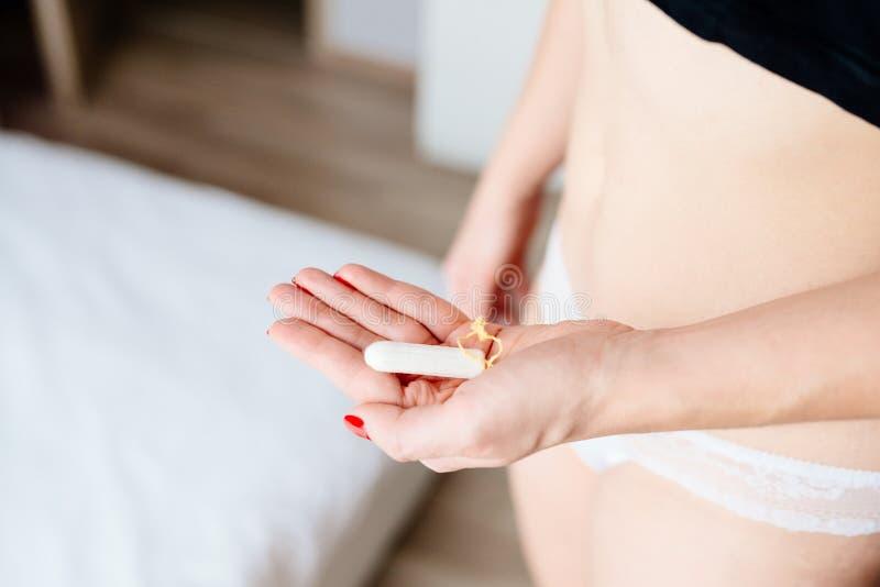 Stäng sig upp på den hållande vita bomullstampongen för kvinnan royaltyfri foto