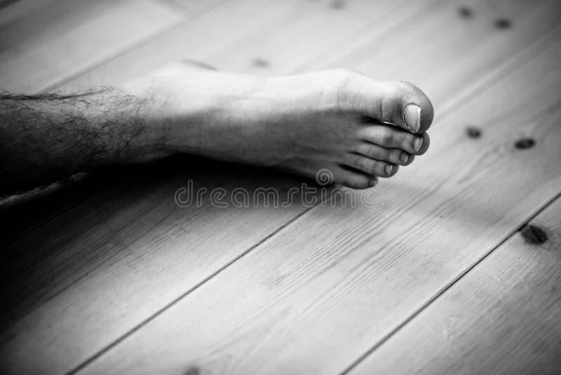 Stäng sig upp på den manliga foten över trägolv royaltyfri fotografi