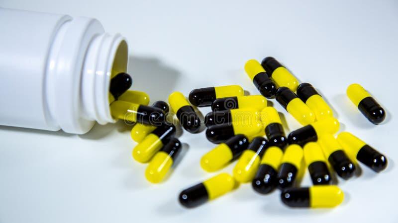 Stäng sig upp på en flaska av receptdroger som ut faller Svarta och gula piller arkivfoton